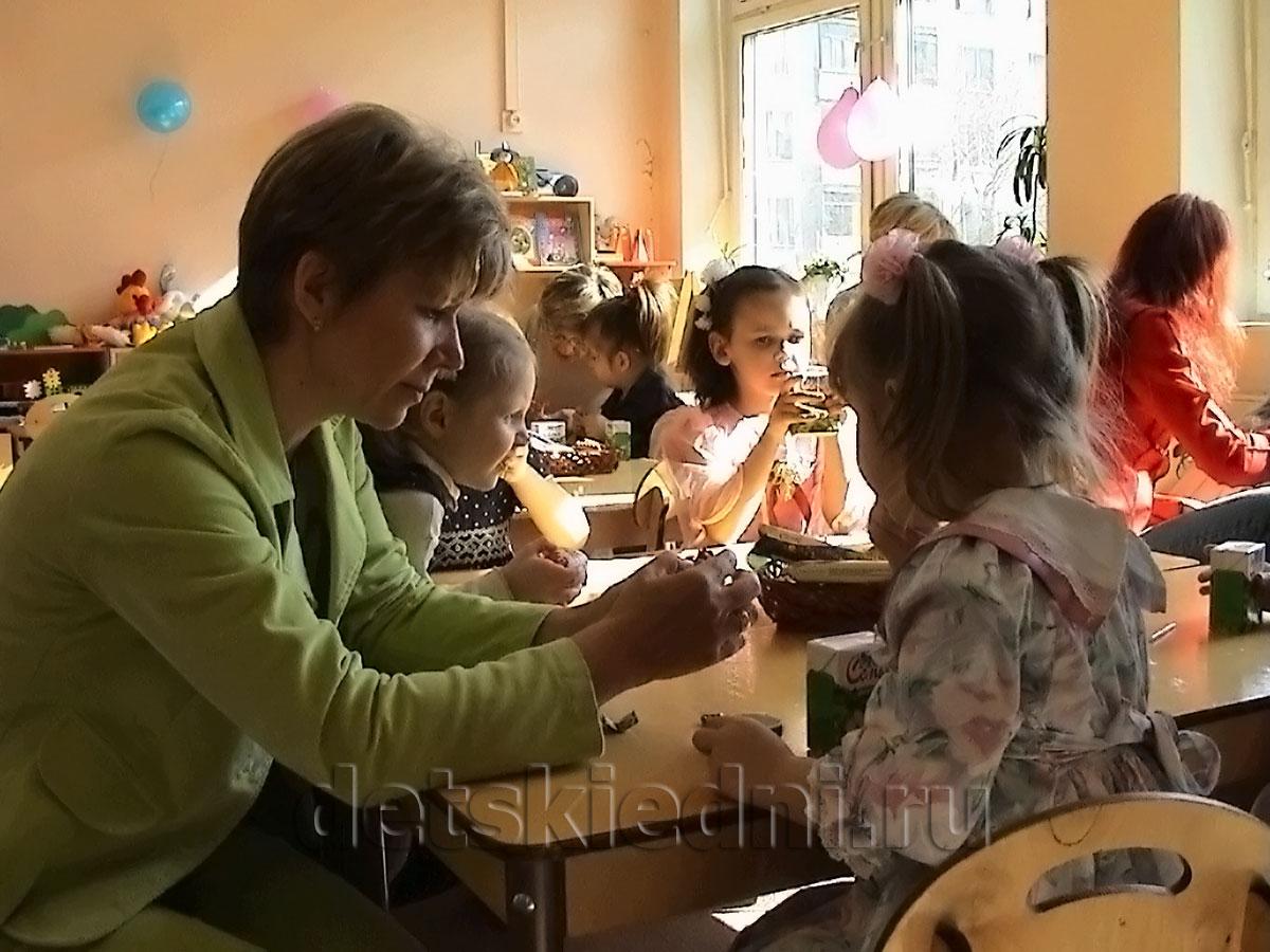 Дети и воспитатель в детском саду.
